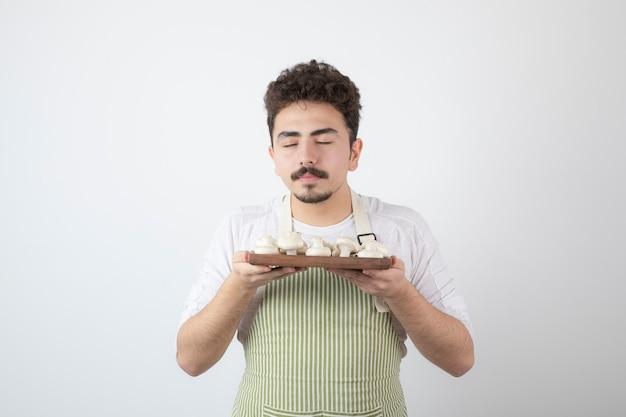 Изображение мужского повара пахнет сырыми грибами на белом