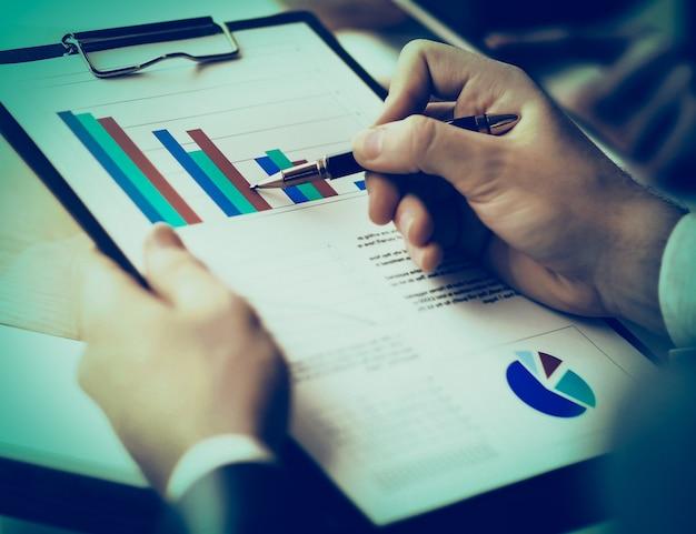 회의에서 토론하는 동안 비즈니스 문서를 가리키는 남성 손 이미지
