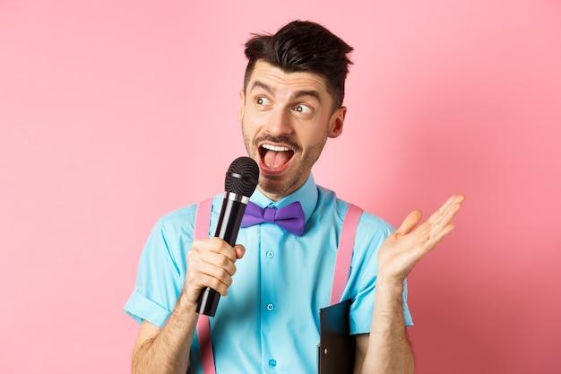남성 쇼 호스트 연설, 겨드랑이 아래 클립 보드와 마이크에서 이야기, 축제 이벤트에 enteratin 사람들, 분홍색 배경 위에 서있는 이미지.
