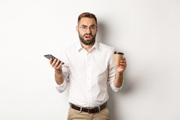 흰색 배경 위에 서서 휴대폰으로 이상한 메시지를 받고 혼란스러워하며 커피를 마시는 남자의 이미지.