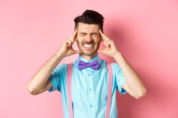 Изображение человека с головной болью, касающегося головных висков, гримасничающего от болезненной мигрени, стиснутого зубами, стоящего больным на розовом фоне.