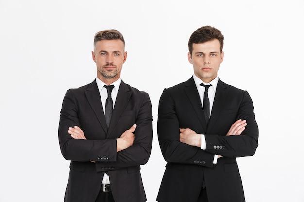 Изображение мужских серьезных двух бизнесменов в офисных костюмах, смотрящих со скрещенными руками
