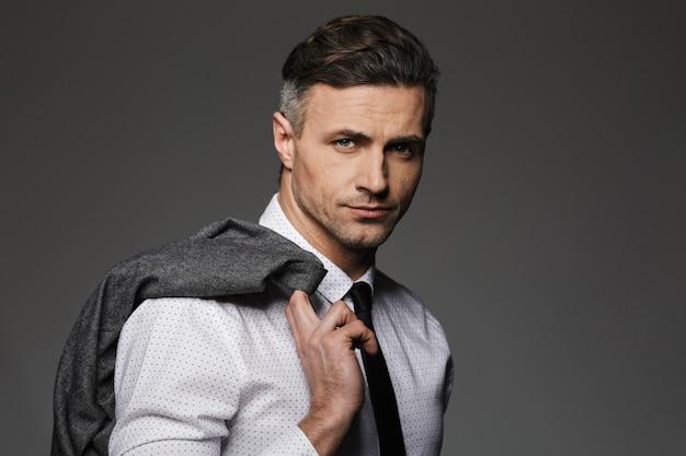 ビジネススーツを着て、灰色の壁に分離された彼の肩にジャケットを保持している成熟した剃っていない男のイメージ