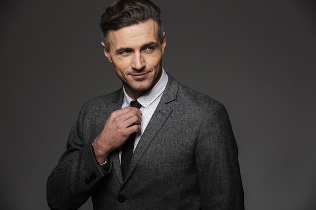 灰色の壁に分離された黒のネクタイを修正しながらよそ見ビジネススーツを着ている成熟した剃っていない男のイメージ