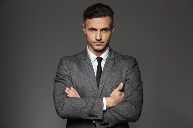 灰色の壁に分離された厳格な決定された視線でビジネススーツを着ている成熟した剃っていない男のイメージ