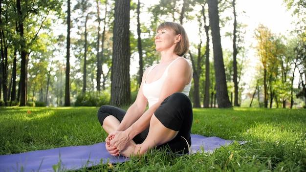 森の芝生で瞑想とヨガの練習をしている中年の笑顔の幸せな女性の画像。フィットネスの練習や公園でのストレッチをしながら心身の健康管理をしている女性