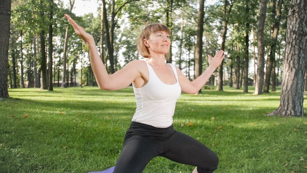Изображение среднего возраста улыбается счастливая женщина медитирует и делает упражнения йоги на траве в лесу. женщина заботится о своем физическом и психическом здоровье, занимаясь фитнесом и растягиваясь в парке