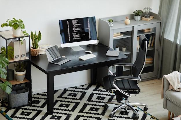 Изображение современного офиса со столом с компьютерным монитором и ноутбуком на его рабочем месте для компьютерного программиста