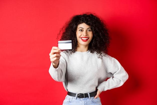 巻き毛、手を伸ばしてプラスチックのクレジットカードを表示し、銀行やショッピングのオファーをお勧めします、赤い背景を持つ現代の女性の画像。
