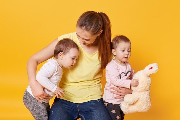 フォトスタジオでポーズをとりながらママと遊んでいる子供を持つ母の画像