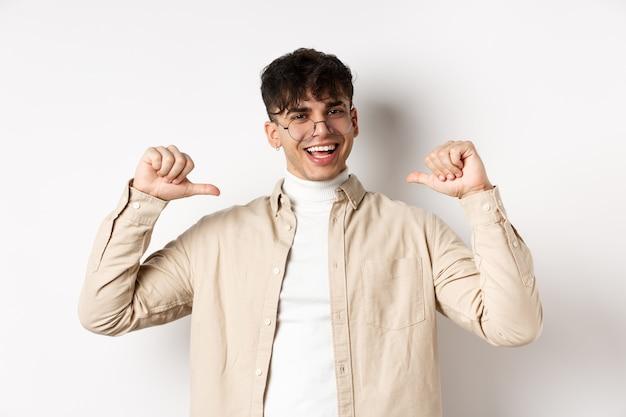 やる気のある笑顔のハンサムな男性が自分自身を指して、自己宣伝し、自信を持って、白い背景の上に立っている画像