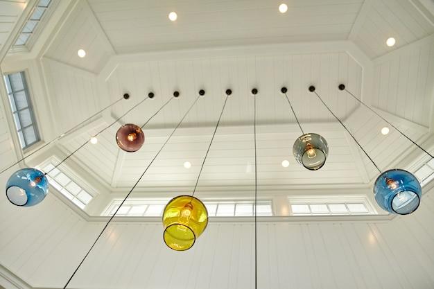天窓から電球がぶら下がっている色とりどりのガラス球の画像