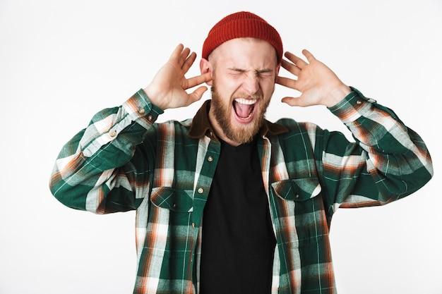 Изображение нервного бородатого парня в шляпе и клетчатой рубашке, кричащего, стоя изолированно на белом фоне