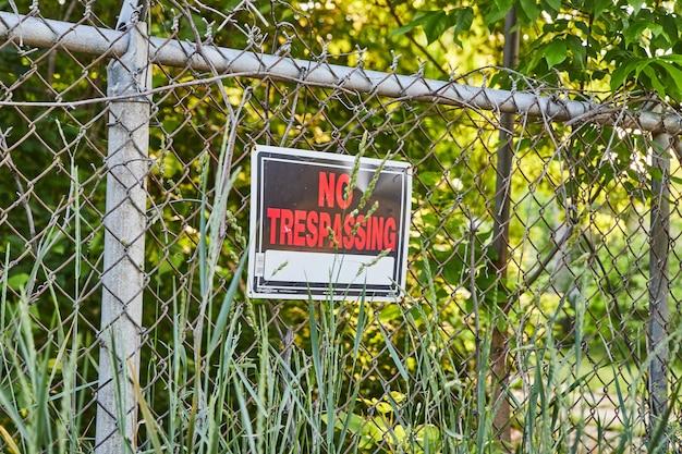 Изображение знака запрета вторжения в красный текст на металлическом заборе в лесу