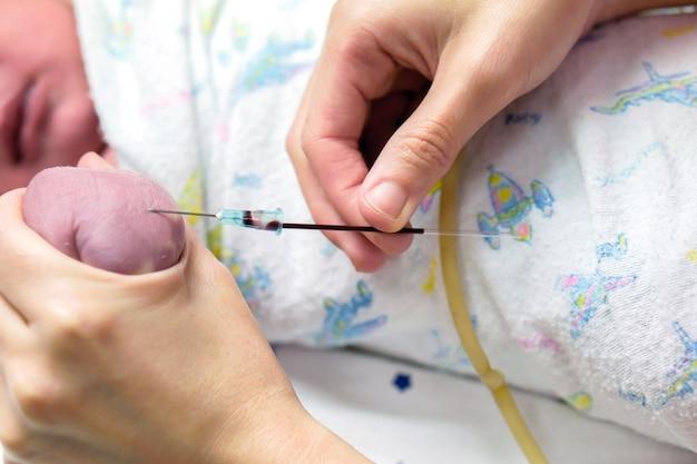 간호사 손의 이미지는 혈액 검사를 하기 위해 아기의 손에 의료 바늘을 점차적으로 찔러 사용합니다.