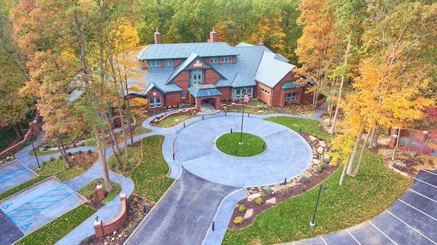 秋の木々に囲まれた円形の私道とオフィス建築の画像