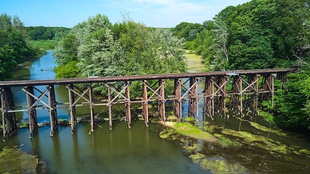 Изображение старой деревянной железной дороги антенны над разделенной рекой в лесу