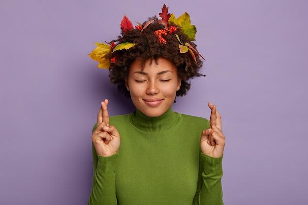 楽観的な幸運の女性の画像は幸運や幸運のために指を交差させ、緑色のタートルネックを着用し、目を閉じたままにします
