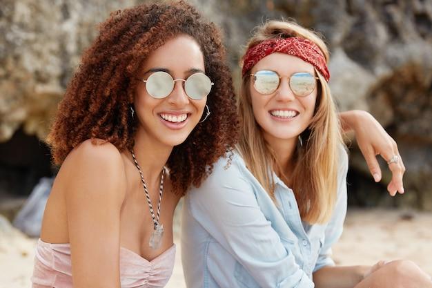 情熱的な同性愛カップルのイメージを受け入れる、流行のサングラスを着用します。美しい暗い肌の若い女性が女性のパートナーを抱擁し、日差しを見て、一緒に座ります。幸せな瞬間。同性関係
