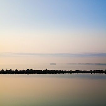 岩だらけの地平線が静かな海に映し出されている静かな湖のシーンの画像