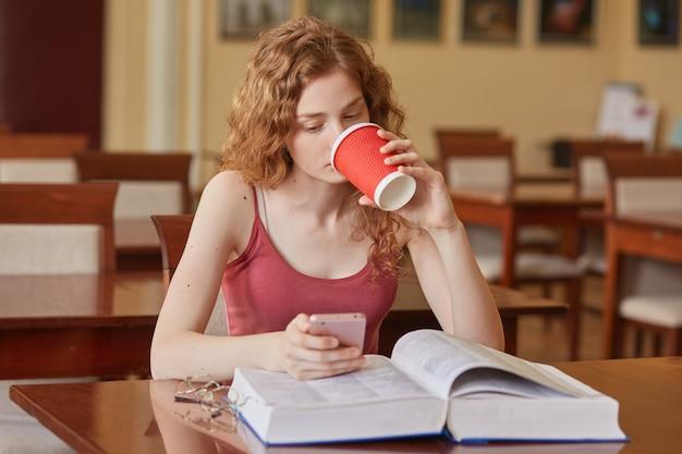 Изображение задумчивой интеллигентной сладкой кудрявые волосы девушка, держа бумажную чашку напитка в одной руке, пить кофе, используя ее смартфон, читать новости, открыв книгу на столе. изучение концепции.