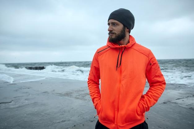 物思いにふける若いブルネットのひげを生やしたスポーツマンが朝のジョギングの後に休憩し、海辺に立って暖かいスポーティな服と帽子をかぶって、ポケットに手を入れている画像