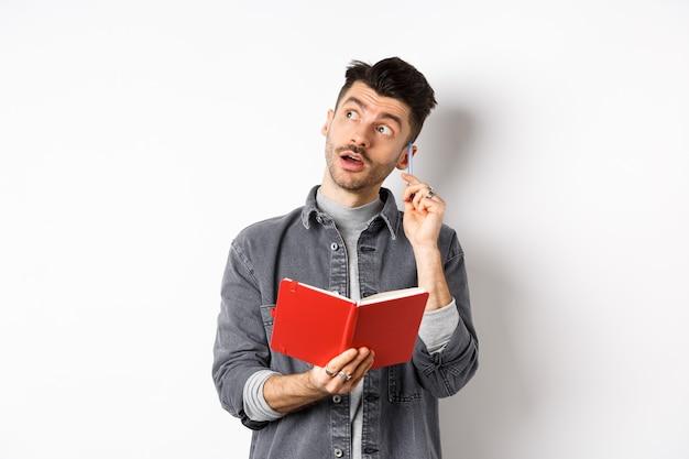 생각에 잠겨있는 젊은 남자 플래너에 아이디어를 적어, 로고를 사려 깊게보고 펜으로 귀를 긁고, 저널을 손에 들고, 흰색 배경의 이미지.