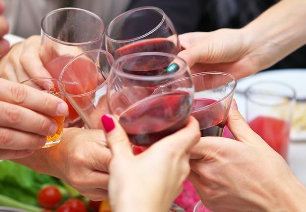 Изображение рук людей с хрустальными бокалами, полными напитков, алкоголя