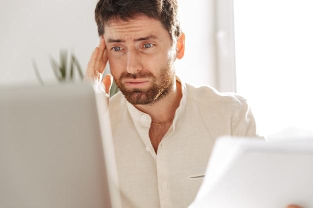 Изображение озадаченного офисного работника 30-х годов в белой рубашке с ноутбуком и бумажными документами, сидящего за столом на современном рабочем месте