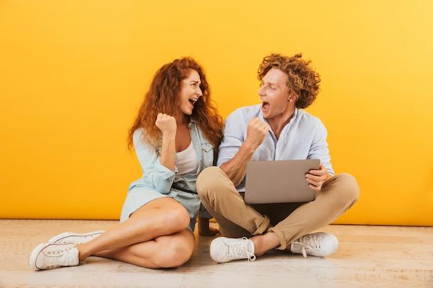 黄色の背景で隔離、床に座って銀のラップトップを使用して満足している素敵なカップルの男性と女性の画像