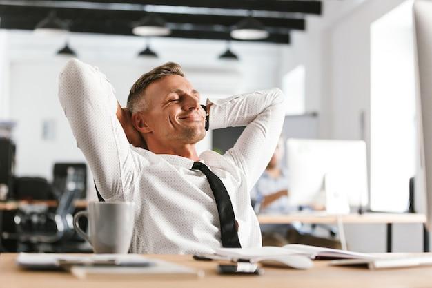 Изображение довольного делового человека средних лет, расслабляющегося, сидя за столом в офисе