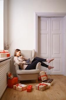 Изображение довольной красивой женщины, держащей кредитную карту с копией пространства с помощью ноутбука