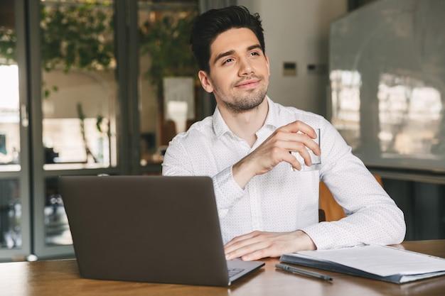 Изображение довольного офисного парня 30-х годов в белой рубашке, сидящего за столом и держащего стакан с водой во время работы на ноутбуке