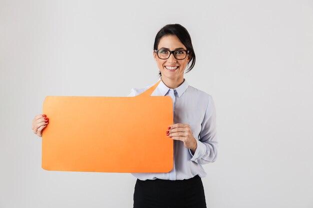 흰 벽 위에 절연 노란색 copyspace 현수막을 들고 안경을 쓰고 기쁘게 사무실 여자의 이미지