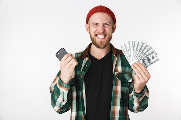흰색 배경 위에 격리 된 서있는 동안 휴대 전화와 달러 돈을 들고 격자 무늬 셔츠를 입고 긍정적 인 남자의 이미지