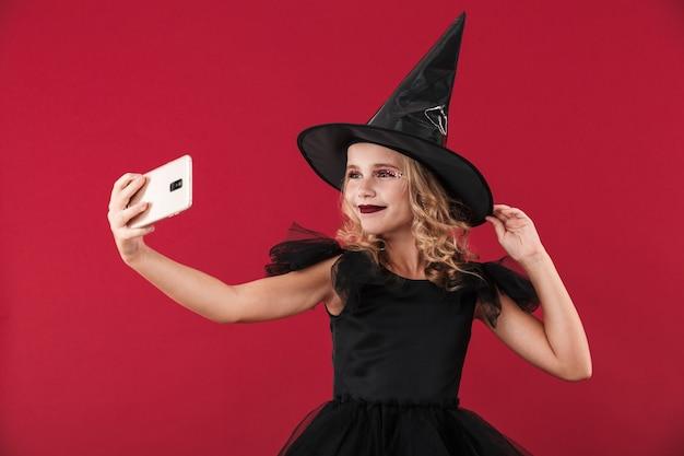 Изображение позитивной счастливой маленькой девочки-ведьмы в карнавальном костюме на хэллоуин