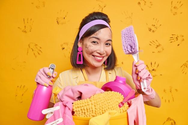 ポジティブな主婦の笑顔のイメージは、掃除道具を心地よく保持し、黄色の壁に対して洗濯物のポーズのバスケットの近くでブラシと洗剤のポーズで作業プロセスのポーズを楽しんでいます
