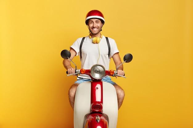 긍정적 인 남성의 이미지는 스쿠터를 타고, 헬멧, 흰색 티셔츠를 입고 좋은 분위기에 있으며 노란색 스튜디오 벽 위에 절연되어 있습니다.