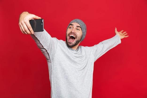 Изображение позитивного мужчины 30 лет в повседневной одежде, смеющегося во время селфи-фото на мобильном телефоне