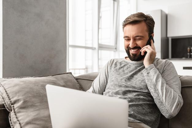 ノートパソコンを使用して携帯電話で話している間、リビングルームのソファーに座っているカジュアルな服装で30代の肯定的な男性の画像
