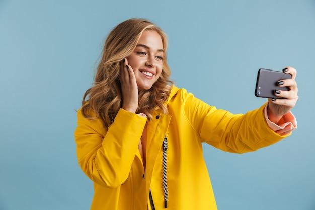 携帯電話を持って自分撮り写真を撮る黄色いレインコートを着ている20代のポジティブな女性の画像