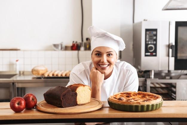 Изображение позитивной женщины-повара в белой форме, позирующей на кухне в кафе с выпечкой