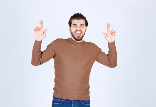 Изображение позитивного молодого человека, изолированного на белом фоне, показывая обнадеживающий, пожалуйста, скрещенными пальцами жест. фото высокого качества
