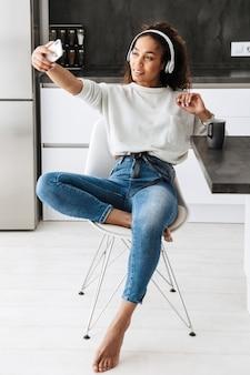 明るいキッチンに座って、自分撮り写真を撮るヘッドフォンを身に着けているかなりアフリカ系アメリカ人の女の子の画像