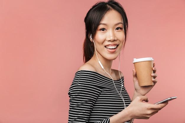 빨간 벽에 격리된 이어폰으로 음악을 들으며 종이컵과 휴대폰을 들고 기본적인 옷을 입은 예쁜 아시아 여성의 이미지