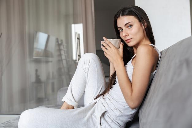 Изображение довольно красивой молодой женщины, сидящей на диване в помещении дома, пить кофе или чай.