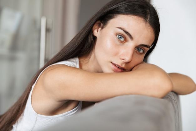 Изображение довольно красивой молодой женщины, сидящей на диване в помещении у себя дома.