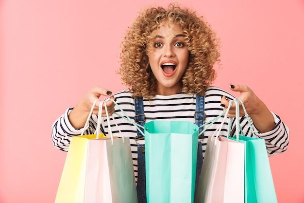 화려한 쇼핑 가방을 들고 캐주얼 옷을 입고 꽤 곱슬 여자 20 대의 이미지