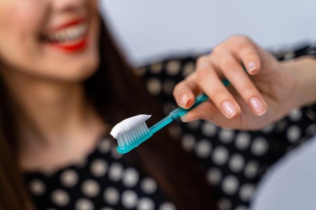 Изображение красивой девушки, держащей зубную щетку в руках. выборочный фокус. концепция ухода за зубами. концепция ухода за полостью рта.