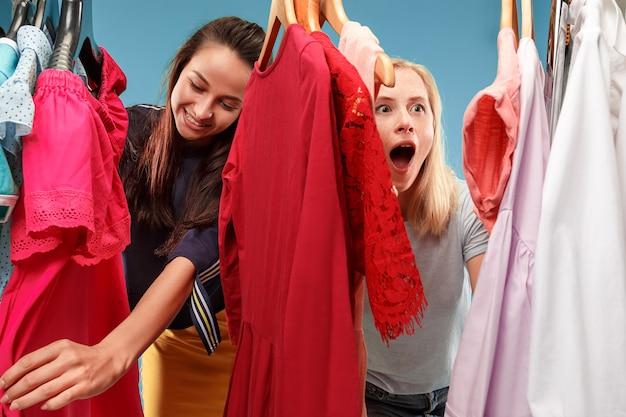 Изображение милых женщин смотря платье пока выбирающ его.